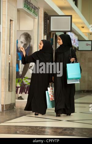Zwei arabische Frauen mit Einkaufstaschen in der Mall zu Fuß. - Stockfoto