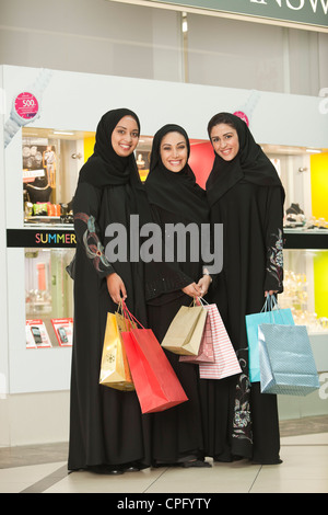 Porträt von drei junge arabische Frauen mit Einkaufstaschen in der Mall, lächelnd. - Stockfoto