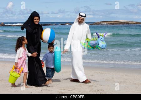 Arabische Familie Hand in Hand bei einem Spaziergang am Strand. - Stockfoto