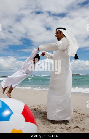Arabische Vater drehte sich um seinen Sohn am Strand. - Stockfoto