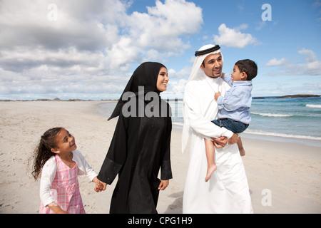 Arabische Familie zusammen am Strand spazieren. - Stockfoto