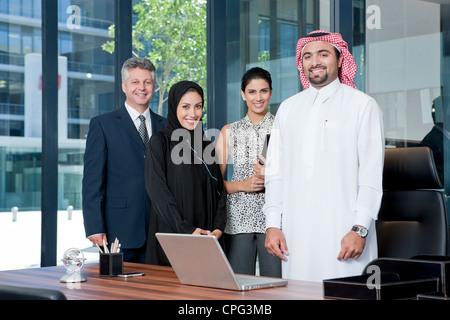 Porträt von Geschäftsleuten im Büro, lächelnd.