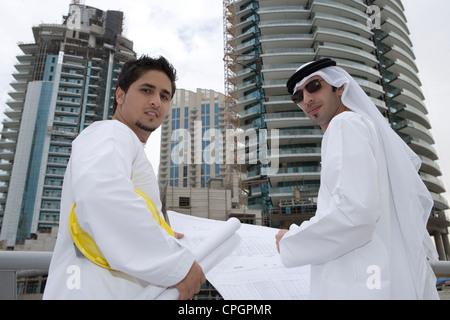 Geschäftsleute mit Blaupausen durch Geländer mit Gebäuden im Hintergrund, Porträt - Stockfoto