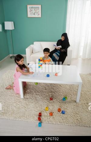 Arabische Mutter lesen, Kinder spielen zu Hause - Stockfoto