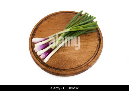 Frühlingszwiebeln auf einer hölzernen Matte - Stockfoto