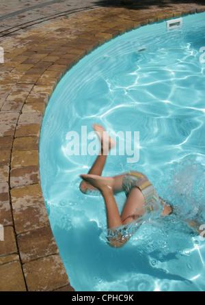 Junge von 7 Jahren warf sich kopfüber in den Pool. - Stockfoto