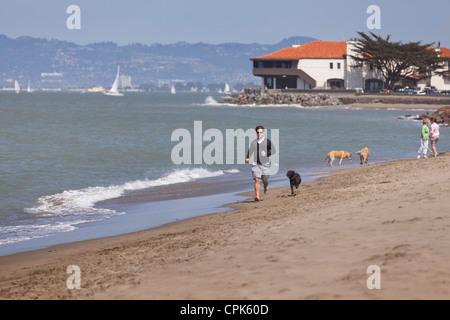 Ein Mann läuft am Strand mit einem Hund - Stockfoto