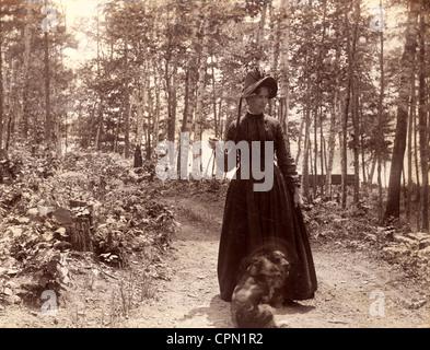Viktorianische Frau mit Hund für einen Spaziergang im Wald Stockfoto