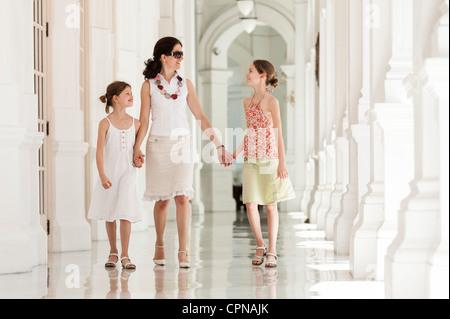 Mutter und Tochter nebeneinander Hand in Hand gehen - Stockfoto