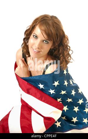 Hübsche junge Frau eingewickelt in eine amerikanische Flagge zeigen ihre 4. Juli Geist und Patriotismus. - Stockfoto