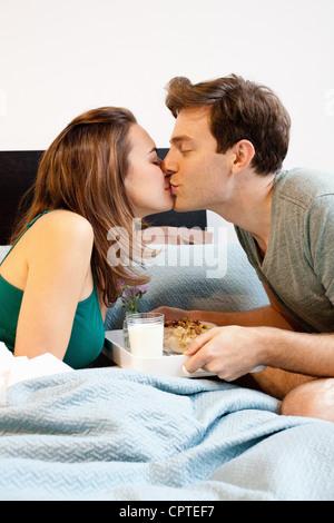 Junge Paar küssen über Frühstückstablett - Stockfoto