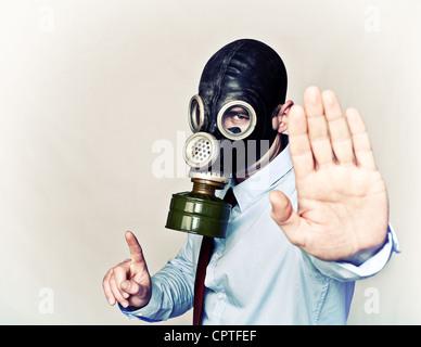 Geschäftsmann mit Gasmaske in Stop-Haltung Stockfoto