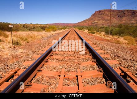 Eisenbahnstrecke neben namenlosen Berg in der Nähe der Stadt von Tom Price in Western Australia. - Stockfoto