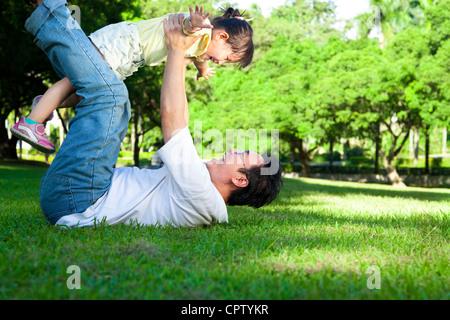 glücklicher Vater und kleine Mädchen auf dem Rasen - Stockfoto