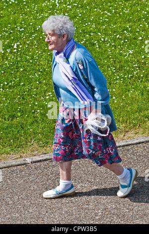 Ältere Frau, die zu Fuß auf Bürgersteig - Frankreich. - Stockfoto