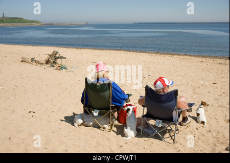 Älteres Ehepaar Sonnenbad zu Tynemouth mit ihren drei Hunden. - Stockfoto