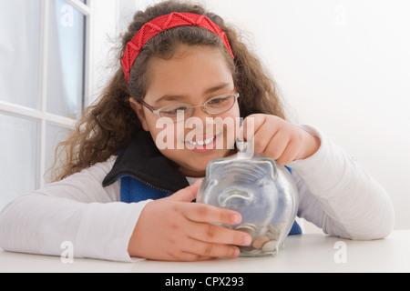 Junges Mädchen einfügen Münzen im Sparschwein - Stockfoto