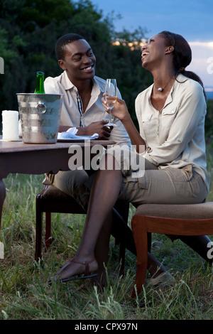 Eine afrikanische paar gemeinsam lachen und trinken Champagner im Freien während des Sonnenuntergangs - Stockfoto