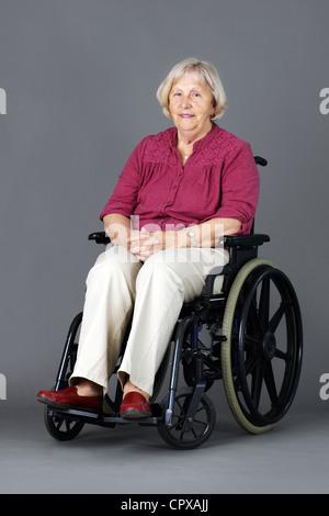 Lächelnde senior Frau sitzt in einem Rollstuhl, Behinderte oder deaktiviert, Blick in die Kamera über neutral grau - Stockfoto