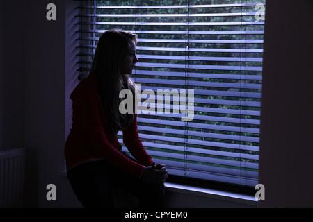 Junge Frau sitzt allein in einem dunklen Raum mit Blick durch ein Fenster Blind. - Stockfoto