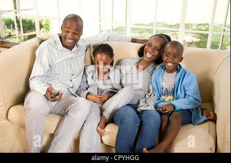 Junge afrikanische Familie sitzen zusammen auf einer couch - Stockfoto