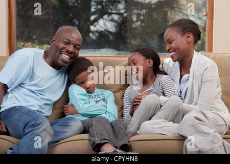 Familie lachen und sitzen auf dem Sofa zusammen, aber Sohn sieht verärgert, Illovo Familie, Johannesburg, Südafrika. - Stockfoto