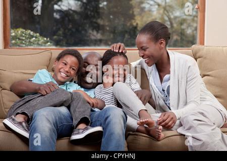 Familie, lachen und sitzen zusammen auf der Couch, Illovo Familie, Johannesburg, Südafrika. - Stockfoto
