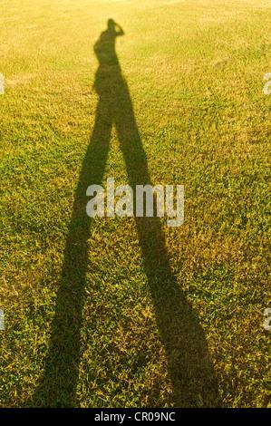 lange Schatten von Menschen auf der Wiese für konzeptionelle Nutzung. - Stockfoto
