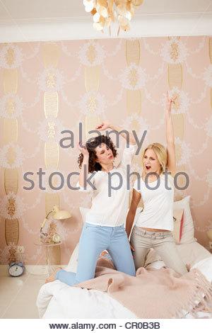 Posierenden Frauen zusammen auf Bett - Stockfoto