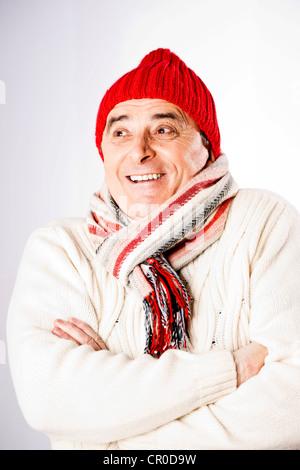 Freundlicher älterer Mann trägt einen Schal und eine wollene Mütze - Stockfoto