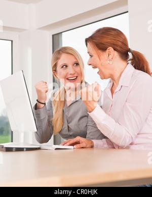 Zwei Frauen jubeln beim Sitzen vor einem computer - Stockfoto