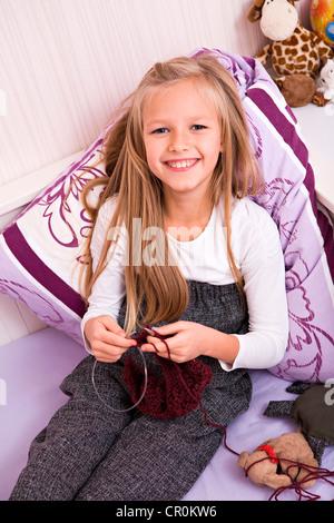 Mädchen auf dem Bett, stricken - Stockfoto