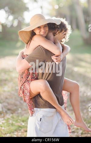 Lächelnde paar umarmt im Feld - Stockfoto