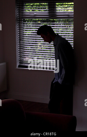 Silhouette des jungen männlichen lehnt gegen eine Wand durch ein Fenster. - Stockfoto