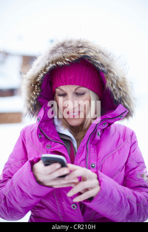 Frau mit Handy im Schnee - Stockfoto