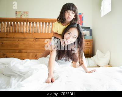 Mutter mit Tochter spielen im Schlafzimmer (4-5) - Stockfoto
