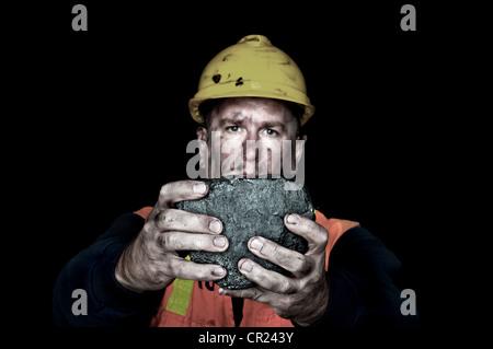 Ein Kohlebergbau hält sich ein großer Teil der Energie reiche Kohle in eine dunkle Kohlemine. - Stockfoto