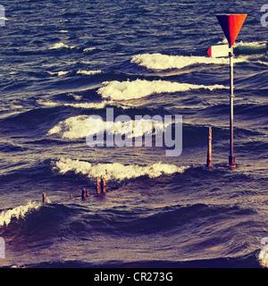 Holz Pfähle im Wasser mit Wellen und ein Warnsignal Stockfoto