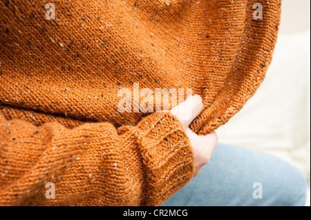 Nahaufnahme von handgestrickten Pullover gestreckt werden, indem Man ihn trägt - Stockfoto