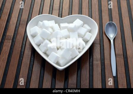 Stück Würfelzucker in einer herzförmigen Porzellanschüssel - Stockfoto