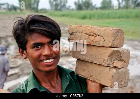 Lächelnde junge Mann mit drei Steinen in einer Hand, Baustelle des einen Bewässerungskanal, Basti Lehar Walla Dorf, - Stockfoto