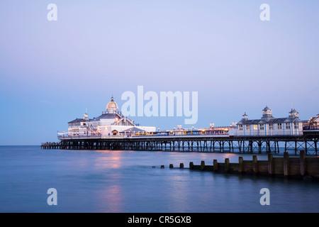 Die Pier in Eastbourne, Sussex, in der Dämmerung an einem Sommerabend klar beleuchtet. - Stockfoto