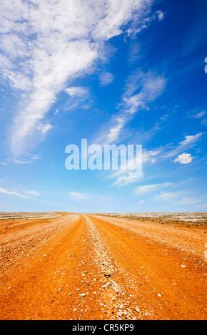 Rote Piste im australischen Outback, unter einem flammenden heißen blauen Himmel. - Stockfoto