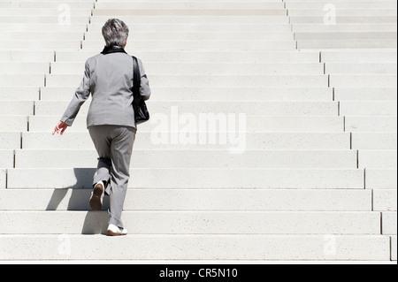 Frau, die Treppe hinauf klettern - Stockfoto