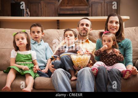 Frontansicht der Familie mit Kindern (18-23 Monate, 4-5, 6-7, 8-9) sitzen auf der Couch vor dem Fernseher und Essen - Stockfoto