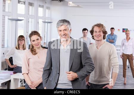 Deutschland, Bayern, München, reifer Mann mit Kollegen im Büro, Lächeln - Stockfoto