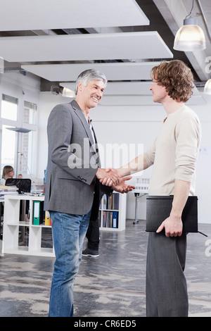 Deutschland, Bayern, München, Männer schütteln Hände im Büro - Stockfoto