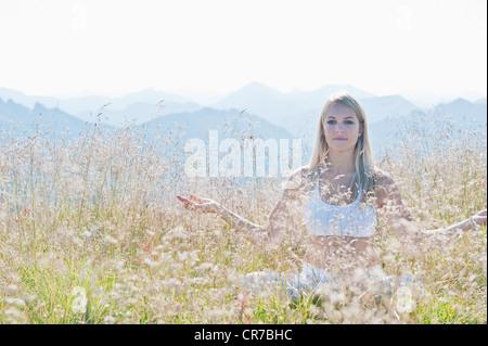Österreich, Salzburger Land, junge Frau sitzt im Almwiese und Meditation zu tun - Stockfoto