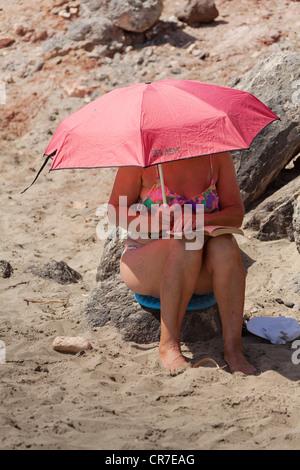Strandleben, Frau unter einem Sonnenschirm, einem guten Buch am Strand, Fuerteventura, Kanarische Inseln, Spanien, - Stockfoto