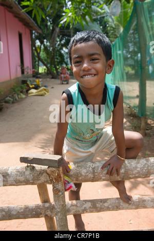 Lächelnde junge Klettern auf einem Zaun mit ihrer Mutter sitzt hinter Kanjippadom, in der Nähe von Alappuzha (Alleppey), - Stockfoto
